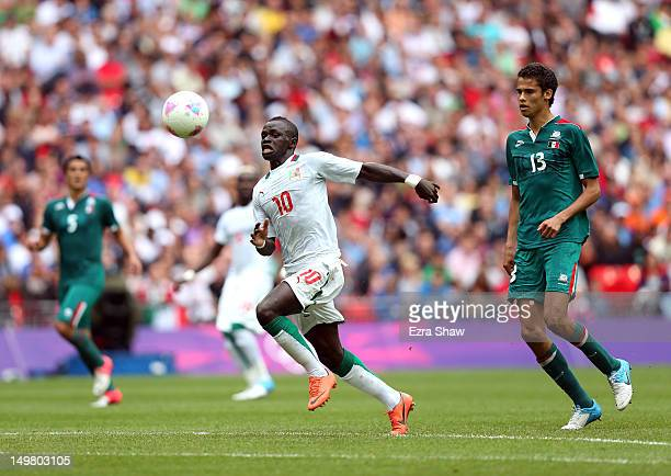 Sadio Mane of Senegal and Diego Reyes of Mexico go for the ball during the Men's Football Quarter Final match between Mexico and Senegal on Day 8 of...