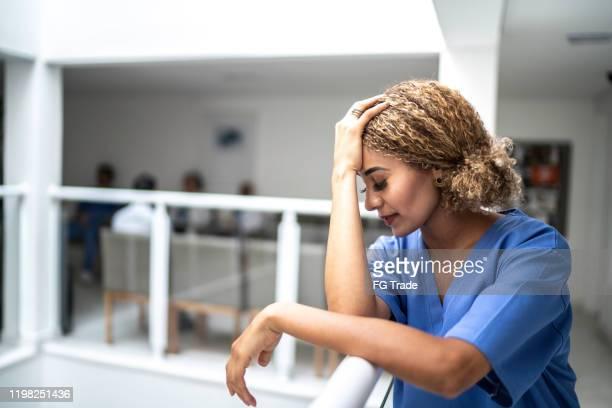 droefheid / ongerust gemaakte vrouwelijke verpleegster bij het ziekenhuis - overwerkt stockfoto's en -beelden