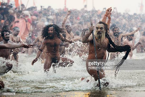 Saduhs or holy men run into the waters of the Sangham or the confluence of the the Yamuna and Ganges rivers during the Kumbh Mela in Allahabad on...