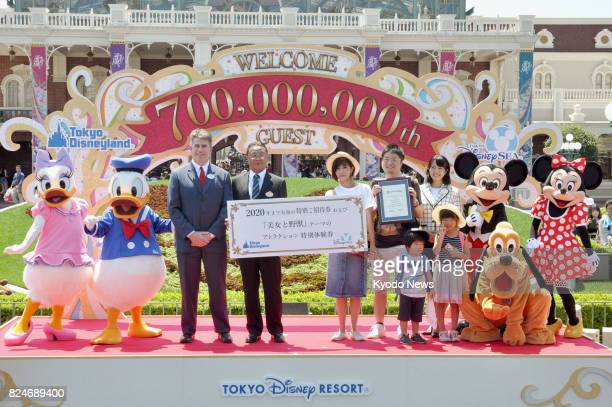 Sae Tanaka holds a certificate marking her as the 700 millionth visitor to Tokyo Disneyland and Tokyo DisneySea in Chiba Prefecture's Urayasu east of...