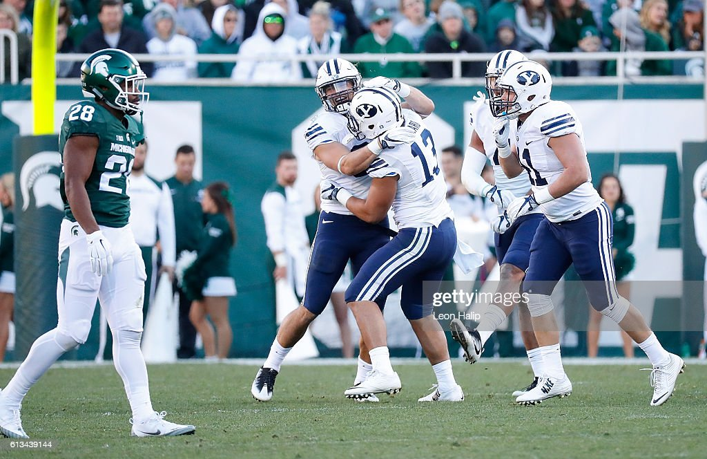 Sae Tautu #31 and Francis Bernard #13 of the Brigham Young Cougars celebrate a third quarter sack of quarterback Tyler O'Connor #7 of the Michigan State Spartans (not in photo) at Spartan Stadium on October 8, 2016 in East Lansing, Michigan. Brigham Young defeated Michigan State 31-14.