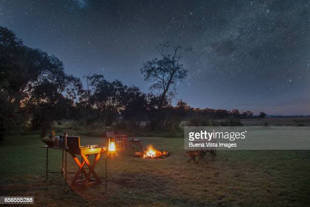 a safari camp at night under starry sky - night safari stock pictures, royalty-free photos & images