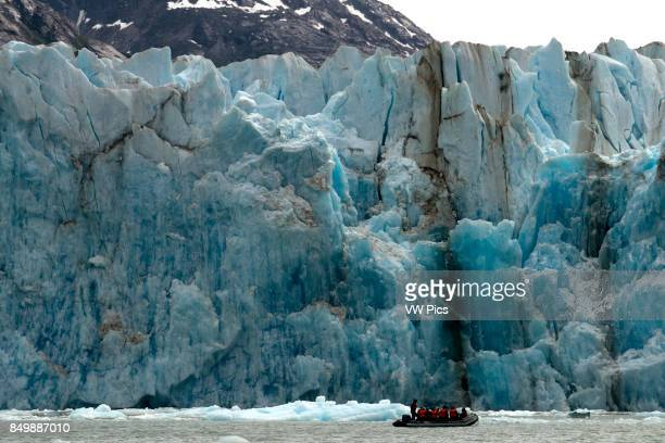 Safari Endeavour cruise passengers in an inflatable boat in front of Dawes Glacier calves into the Endicott Arm fjord of Tracy Arm in Fords Terror...