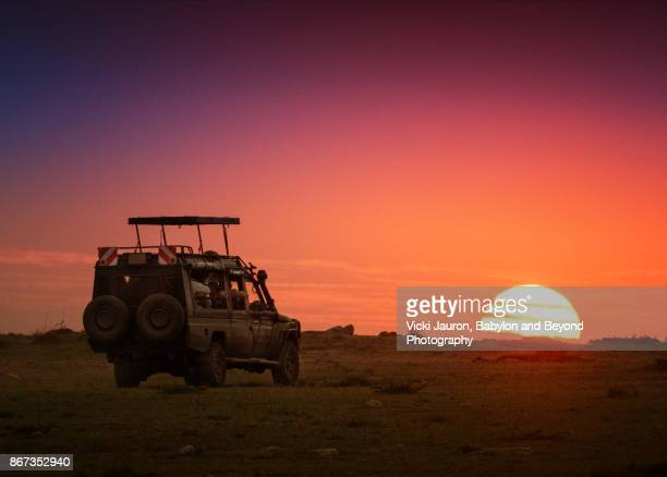 safari vehicle driving into sunrise at masai mara, kenya - kenya stock pictures, royalty-free photos & images