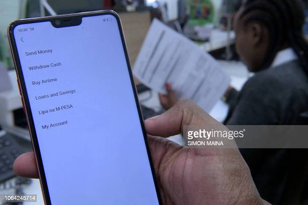 A Safaricom employee displays the MPesa money transfer service on a smartphone inside a mobile phone care centre in Nairobi on November 22 2018