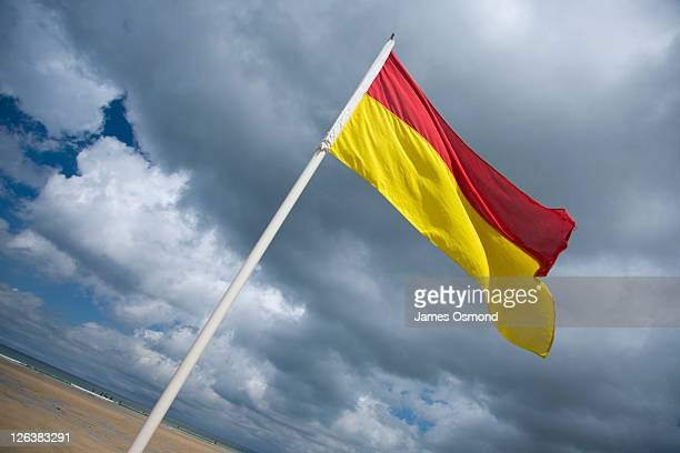 safe bathing flag on the sand at newquay beach, a popular spot for surfers and swimmers to enjoy the water - cornish flag stock pictures, royalty-free photos & images