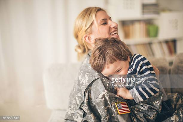 safe in mommy soldier's hug - american culture stock pictures, royalty-free photos & images