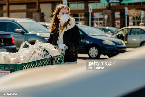 safe shopping practice in times of pandemic viral outbreak.  a young woman wearing a protective mask and gloves walking with a shopping cart to her car on a supermarket's parking lot. - alex potemkin coronavirus stock pictures, royalty-free photos & images