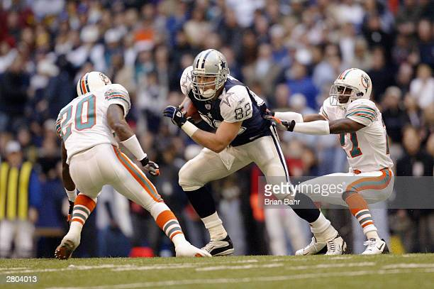 Safety Arturo Freeman and cornerback Terrell Buckley of the Miami Dolphins try to bring down tight end Jason Witten of the Dallas Cowboys on November...