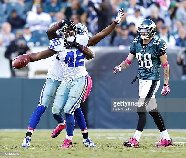 Safety Barry Church of the Dallas Cowboys celebrates an interception with teammate cornerback Morris Claiborne as wide receiver Jeff Maehl of the...