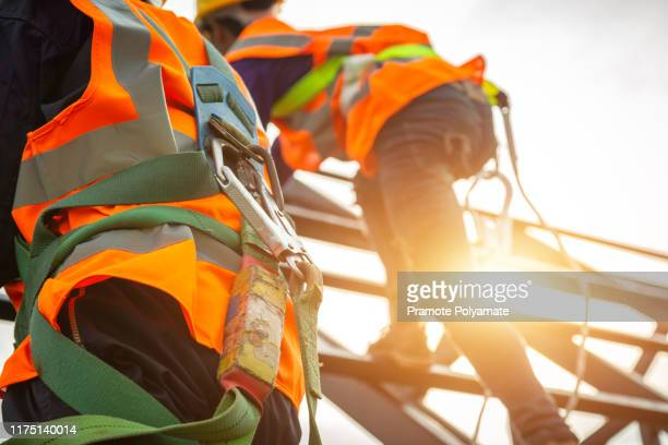 [safety body construction] working at height equipment. fall arrestor device for worker with hooks for safety body harness on selective focus. worker as in construction background. - safety harness stock pictures, royalty-free photos & images