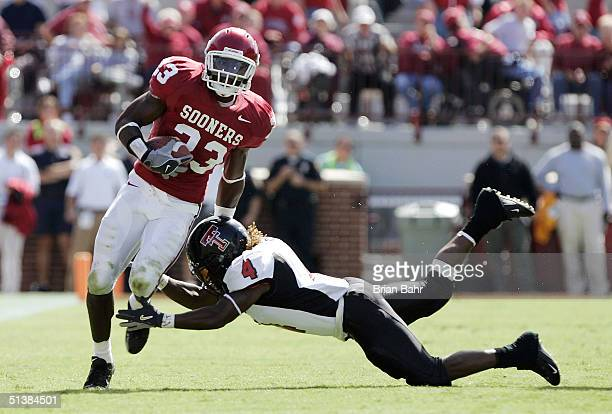 Safety Brodney Pool of the Oklahoma Sooners slips through the arms of running back Johnnie Mack of the Texas Tech Red Raiders with an interception in...