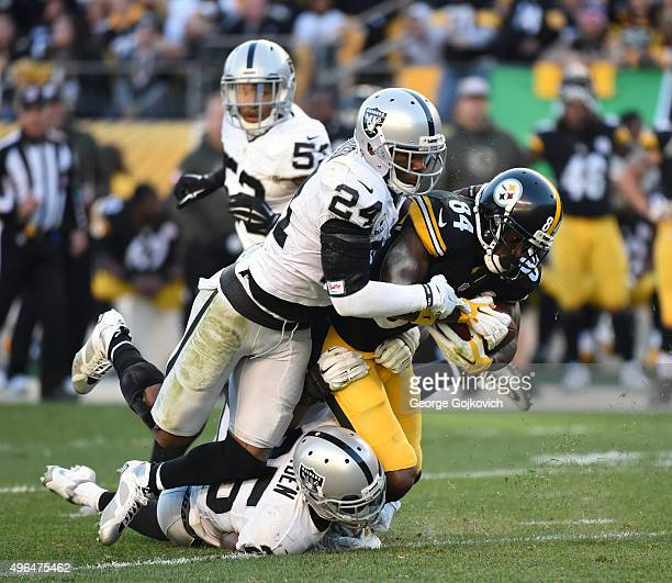 Safety Charles Woodson and cornerback DJ Hayden of the Oakland Raiders tackle wide receiver Antonio Brown of the Pittsburgh Steelers during a game at...