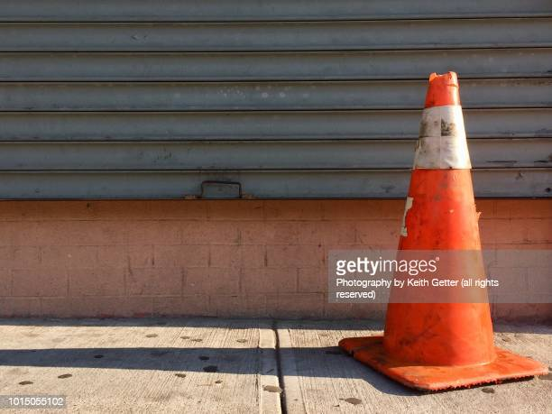 a safety cone in front of a closed metal gate - traffic cone stock pictures, royalty-free photos & images