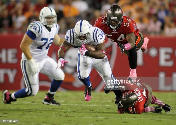 Safety Corey Lynch and Linebacker Geno Hayes of the Tampa Bay Buccaneers bring down Running back Delone Carter of the Indianapolis Colts at Raymond...