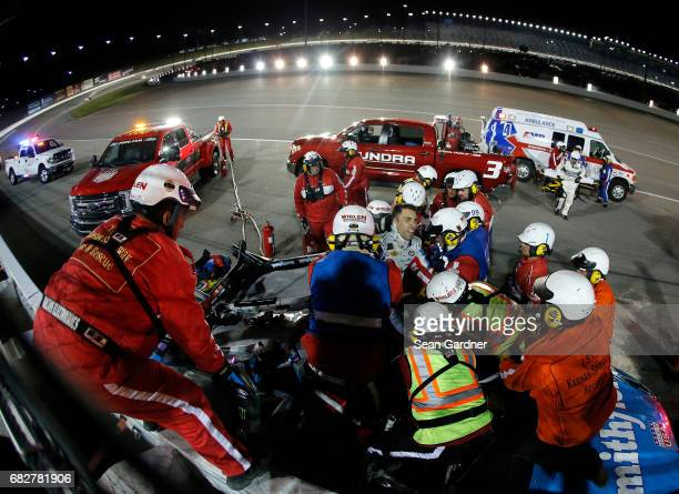 Safety crew workers place Aric Almirola driver of the Smithfield Ford on a stretcher after cutting off the roof of his car after a crash during the...