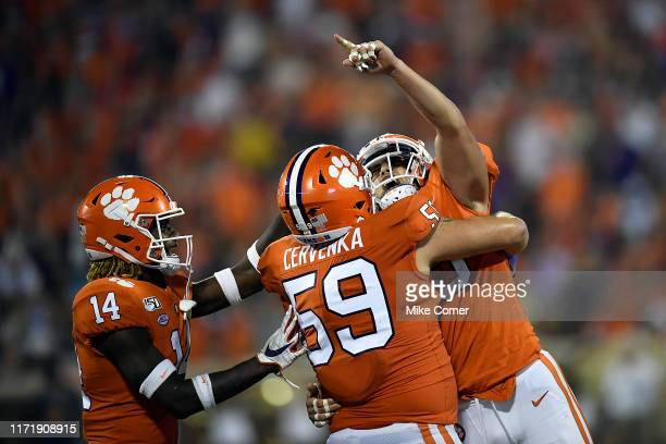 Safety Denzel Johnson defensive tackle Jordan Williams and Safety Tanner Muse of the Clemson Tigers celebrate after Muse makes an interception...
