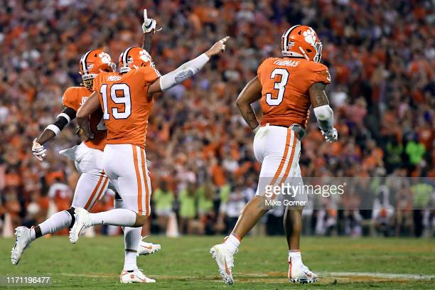 Safety Denzel Johnson safety Tanner Muse and defensive end Xavier Thomas of the Clemson Tigers celebrate after Johnson makes an interception against...