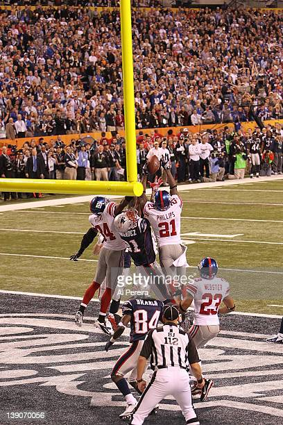 Safety Deon Grant and Safety Kenny Phillips of the New York Giants break up a Hail Mary Pass in the end zone intended for Tight End Aaron Hernandez...