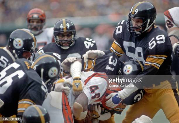 Safety Donnie Shell and linebacker Jack Ham of the Pittsburgh Steelers tackle running back Pete Johnson of the Cincinnati Bengals with assistance...