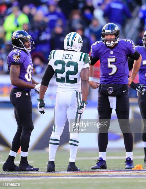 Safety Ed Reed of the New York Jets talks with quarterback Joe Flacco and wide receiver Torrey Smith of the Baltimore Ravens during the second half...