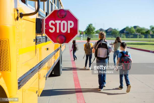safety equipment keeps children safe as they walk toward bus - school bus stock pictures, royalty-free photos & images