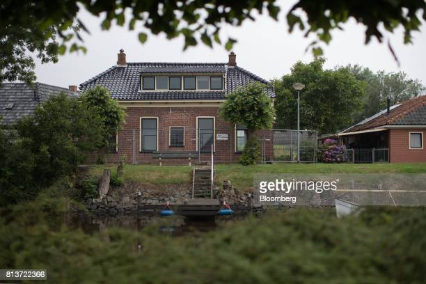 A safety fence stands around perimeter of an uninhabitable house affected by fracking owned by Hiltje Zwartberg in Termunterzijl Groningen...