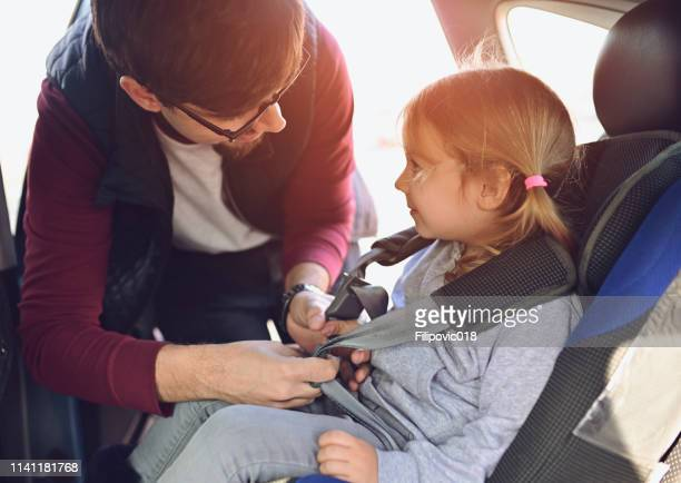 safety first, father puts child in car seat - buckle stock pictures, royalty-free photos & images