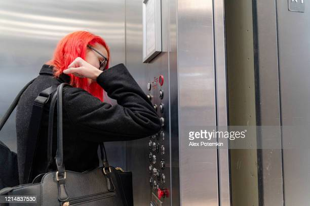 safety first. in times of pandemic, you have to make precautions handling elevators to prevent disease spreading. teenager girl pressing the button using her elbow. - alex potemkin coronavirus stock pictures, royalty-free photos & images