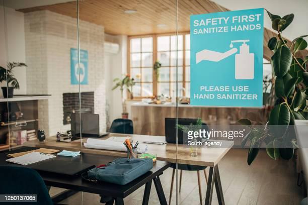 安全第一、空の近代的なオフィスでガラスに手のサインを消毒 - 予防 ストックフォトと画像