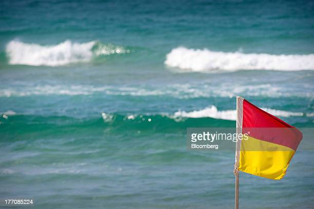 A safety flag stands on Main Beach on the Gold Coast Australia on Saturday Aug 17 2013 The Reserve Bank of Australia this month reduced its growth...