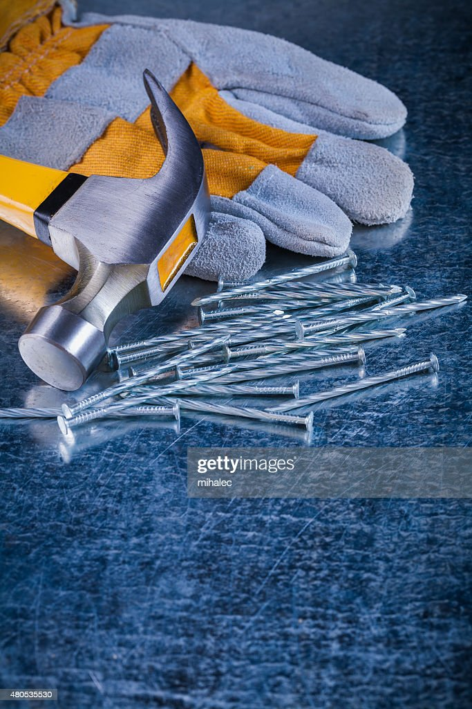 Safety glove collection of metal nails and claw hammer on : Stock Photo