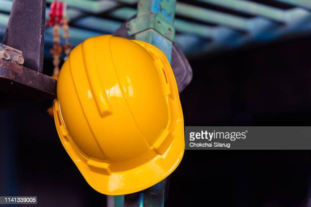safety helmet hat hung on construction site - yellow hat stock pictures, royalty-free photos & images