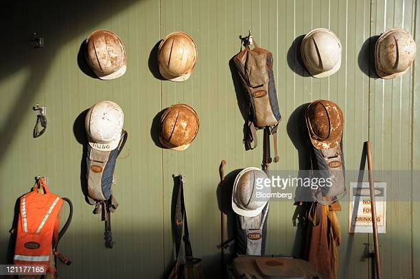 Safety helmets and CamelBak Products LLC backpacks hang on a wall outside a lunch break station at Fortescue Metals Group Ltd's Cloudbreak iron ore...