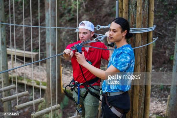 Instrutor de segurança, preparar um homem para ir em uma linha de fecho de correr pela floresta