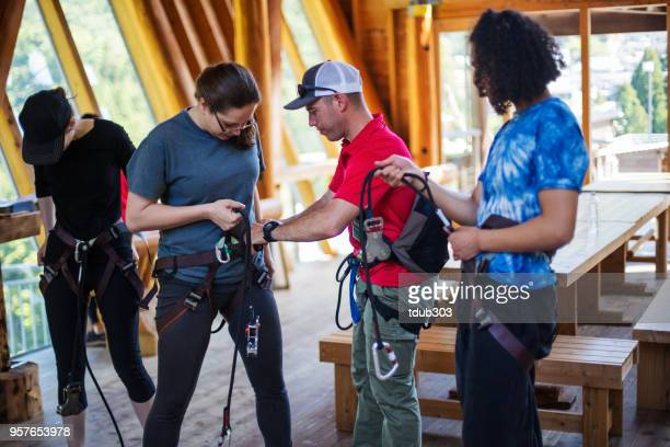 Safety instructor teaching how to use a safety harness for an adventure park