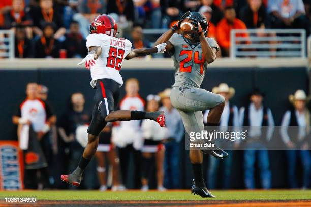 Safety Jarrick Bernard of the Oklahoma State Cowboys intercepts a pass against wide receiver KeSean Carter of the Texas Tech Red Raiders to set up a...