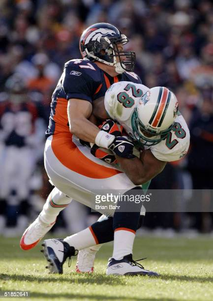 Safety John Lynch of the Denver Broncos stops running back Travis Minor of the Miami Dolphins in the first half on December 12 2004 at Invesco Field...