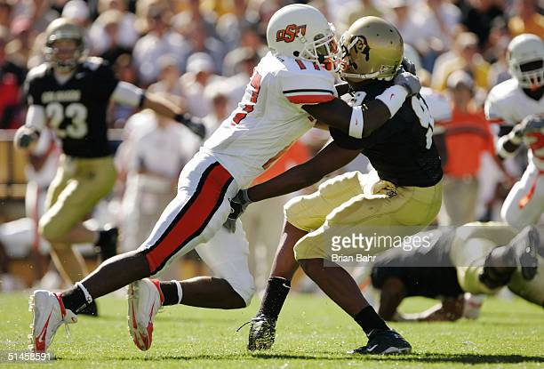 Safety Jon Holland of the Oklahoma State Cowboys levels Blake Mackey of the Colorado Buffaloes in the first half October 9, 2004 at Folsom Field in...