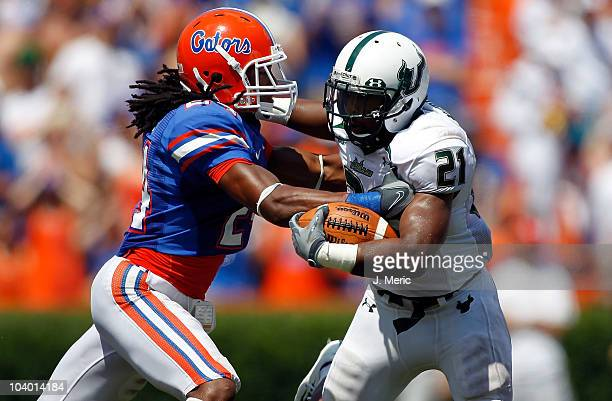 Safety Josh Evans of the Florida Gators tackles running back Demetris Murray of the South Florida Bulls during the game at Ben Hill Griffin Stadium...