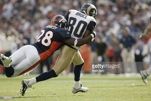 Safety Kenoy Kennedy of the Denver Broncos tackles wide receiver Isaac Bruce of the St Louis Rams during the NFL game on September 8 2002 at Mile...