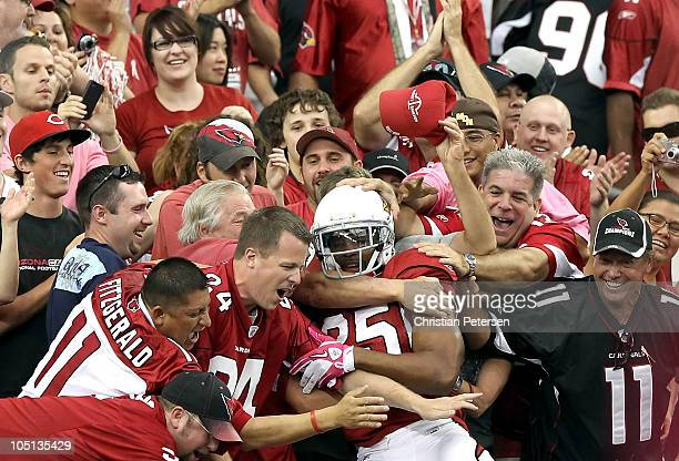 Safety Kerry Rhodes of the Arizona Cardinals celebrates with fans after scoring a touchdown on a fumble recovery during the fourth quarter of the NFL...