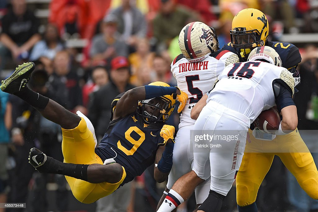 Safety KJ Dillon #9 of the West Virginia Mountaineers tries to pull down quarterback C.J. Brown #16 of the Maryland Terrapins in the first quarter during an NCAA college football game at Capital One Field at Byrd Stadium on September 13, 2014 in College Park, Maryland.