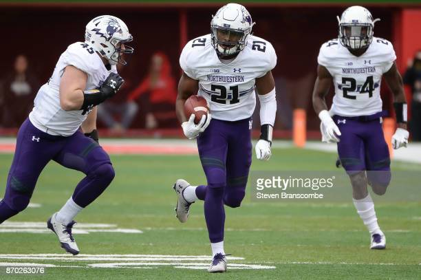 Safety Kyle Queiro of the Northwestern Wildcats returns an interception with linebacker Nathan Fox and cornerback Montre Hartage against the Nebraska...