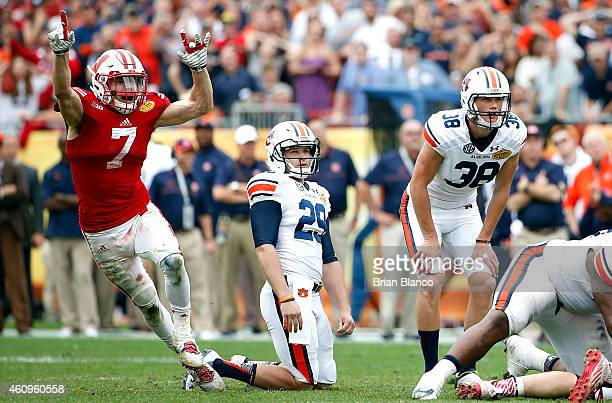Safety Michael Caputo of the Wisconsin Badgers celebrates as place kicker Daniel Carlson of the Auburn Tigers and punter Tyler Stovall watch as...