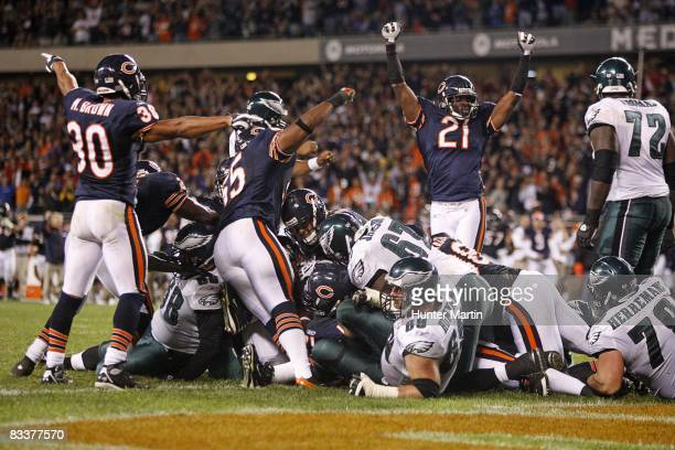 Safety Mike Brown linebacker Lance Briggs and cornerback Corey Graham of the Chicago Bears celebrate after stopping the Philadelphia Eagles from...