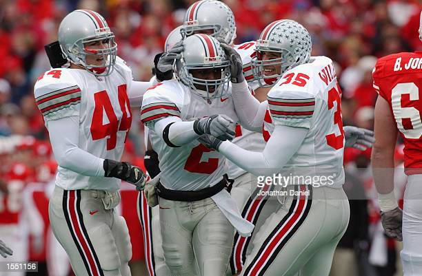 Safety Mike Doss of Ohio State celebrates a fumble recovery with linebacker teammates Matt Wilhelm and Robert Reynolds during the NCAA football game...