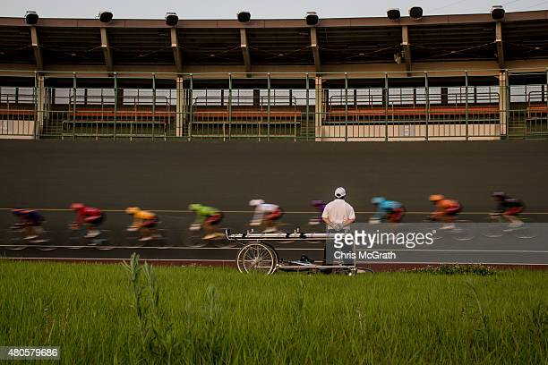 A safety officer stands next to a stretcher as riders pass by during a Keirin race at the Kawasaki Velodrome on July 11 2015 in Kawasaki Japan Keirin...