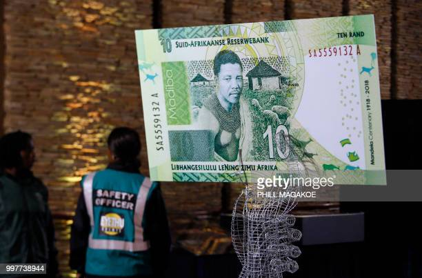 Safety officers stand next to a large banknote at the value of ten rand depicting former South African president Nelson Mandela at Freedom Park on...