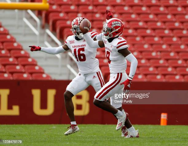 Safety Percy Butler of the Louisiana-Lafayette Ragin Cajuns celebrates with teammate cornerback Asjlin Washington of the Louisiana-Lafayette after...